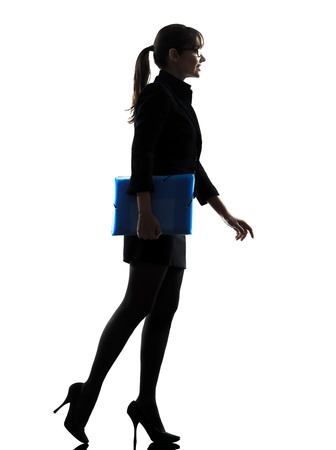 one caucasian business business woman  holding folders files walking silhouette in silhouette studio isolated on white background photo