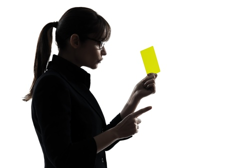 one caucasian business woman showing yellow card  in silhouette studio isolated on white background Stock Photo - 18632771