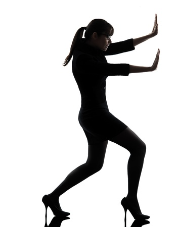 one caucasian business woman pushing in silhouette studio isolated on white background Stock Photo - 18632794