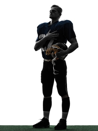 one caucasian american football player man hand on heart in silhouette studio isolated on white background photo