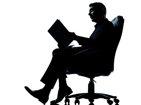 man side view: one caucasian business man sitting in armchair reading ancient book silhouette Full length in studio isolated on white background