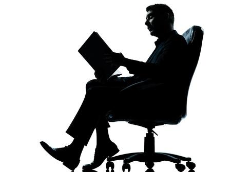 hombre escribiendo: un hombre de negocios cauc�sico que se sienta en el libro de lectura del antiguo sill�n silueta de cuerpo entero en el estudio aislado sobre fondo blanco Foto de archivo