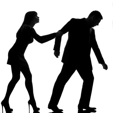 separation: one caucasian couple dispute separation man leaving and woman holding back in studio silhouette isolated on white background