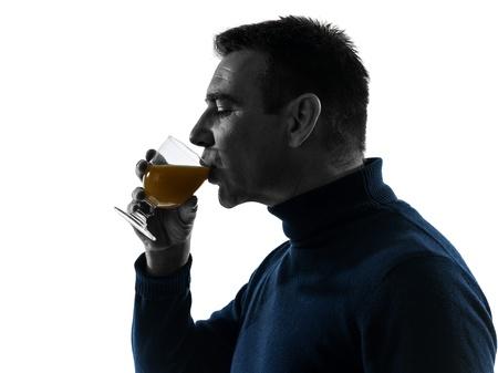 side profile: one caucasian man drinking orange juice  portrait in silhouette studio isolated on white background