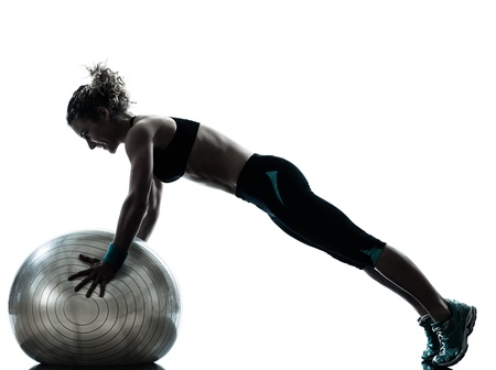 pushups: one caucasian woman exercising fitness ball workout posture in silhouette studio isolated on white background
