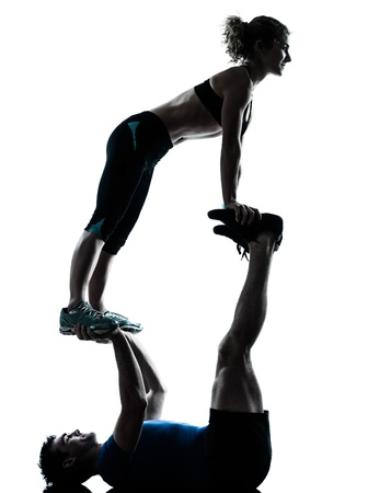 acrobatic: one caucasian couple man woman personal trainer coach exercising acrobatic silhouette studio isolated on white background