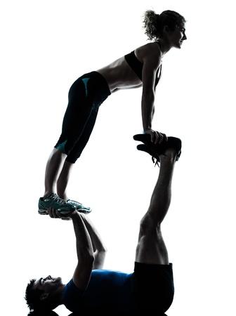 acrobacia: un hombre caucásico mujer entrenador personal trainer acrobático ejercicio de estudio silueta aislado en el fondo blanco Foto de archivo