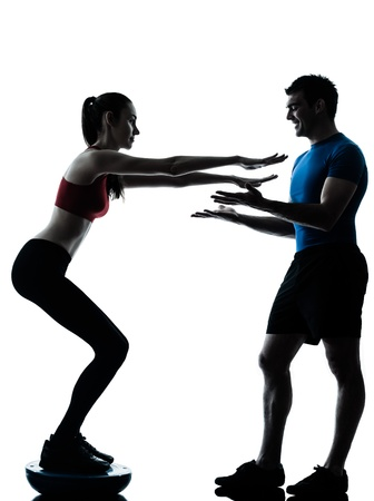 crouches: personal trainer man coach and woman exercising squats on bosu silhouette  studio isolated on white background Stock Photo