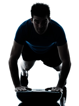 one caucasian man exercising push ups on bosu workout fitness in silhouette studio  isolated on white background photo