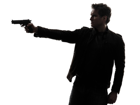 male killer: one man killer policeman aiming gun silhouette studio white background Stock Photo