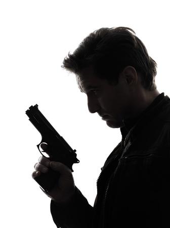 pistola: un hombre polic�a asesino sosteniendo la pistola retrato silueta white background