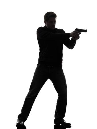 pistols: one man killer policeman aiming gun standing silhouette studio white background Stock Photo