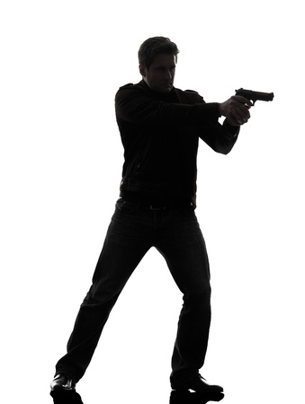 pistola: un hombre de pie con el objetivo polic�a asesino pistola silueta white background