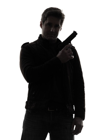 man holding gun: one man killer policeman holding gun portrait silhouette studio white background Stock Photo