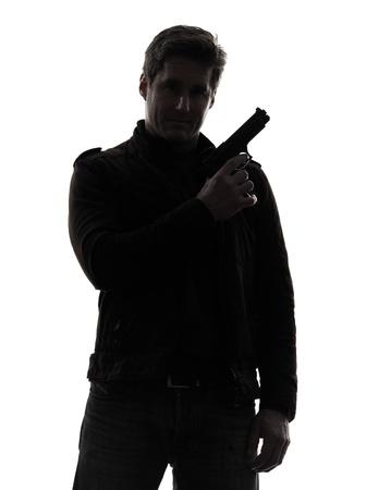 man holding gun: one man killer policeman holding gun portrait silhouette studio white background Stock Photo