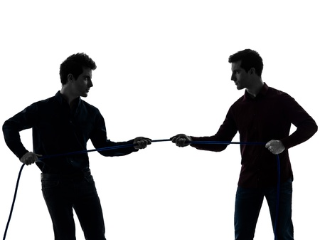 self worth: two caucasian young men tug of war  in shadow  white background Stock Photo