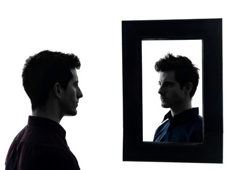 esquizofrenia: hombre delante de su espejo en la sombra de fondo blanco