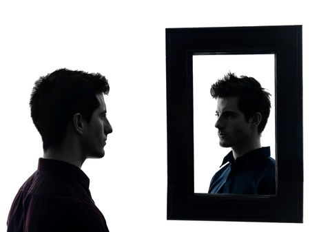 looking in mirror: man in front of his mirror  in shadow  white background