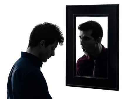 faccia disperata: l'uomo di fronte al suo specchio nel fondo ombra bianca