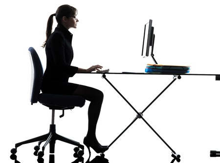 sitting at desk: one business woman computer computing typing  silhouette studio isolated on white background