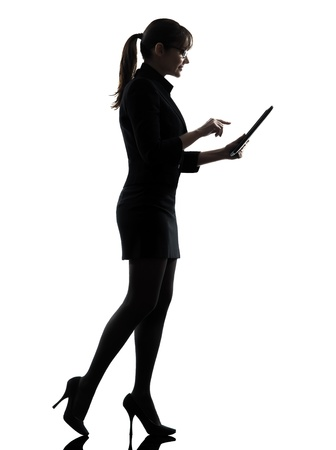 profile view: one business woman walk g computer computing typing digital tablet  silhouette studio isolated on white background