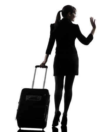 going: one business woman traveler saluting  rear view  silhouette studio isolated on white background