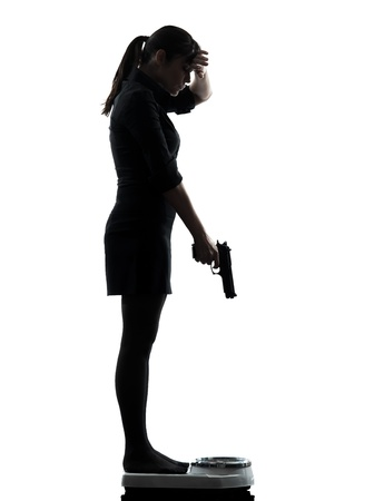 one woman standing on weight scale despair aiming gun silhouette studio isolated on white background photo
