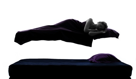 levitation: one woman sleeping in levitation on bed silhouette studio on white background Stock Photo