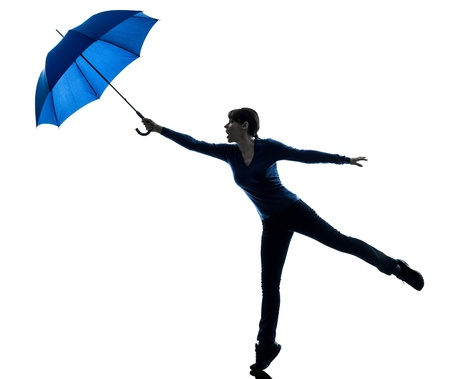 viento soplando: una mujer cauc�sica que sostiene el paraguas viento que sopla en el estudio de la silueta aislado en el fondo blanco