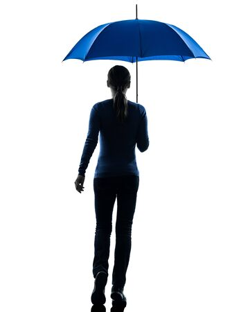 one caucasian woman rear view walking  holding umbrella  in silhouette studio isolated on white background photo