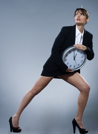 beautiful woman on isolated backgound holding a clock photo