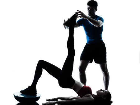 abdominals: personal trainer man coach and woman exercising abdominals push ups on bosu silhouette  studio isolated on white background