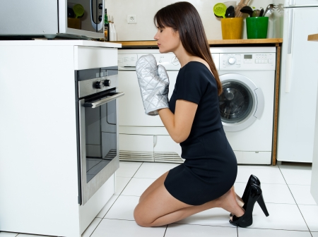 to implore: beautiful caucasian woman in a kitchen waiting with anxiety in front of the oven