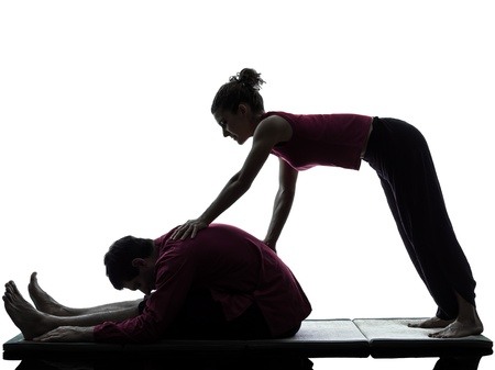one man and woman performing thai massage in silhouette studio on white background photo