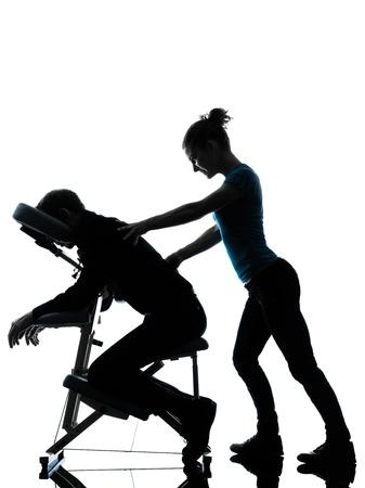 masaje: un hombre y la mujer la realizaci�n posterior de la silla de masaje en el estudio de la silueta sobre fondo blanco