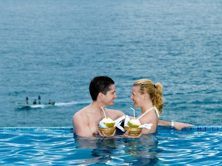beautiful caucasian couple enjoying their vacation in a swimming pool by the seaside drinking coconut milk photo