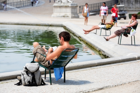 tourist resting and reading in a park of paris during summer heat wave Editorial