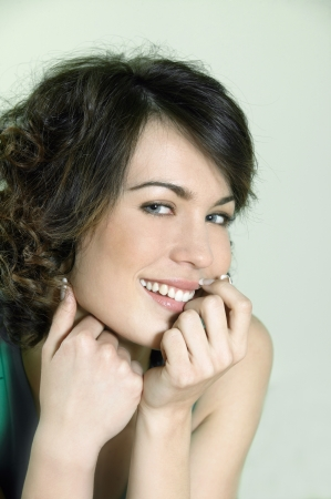 shyness: studio shots portrait of a beautiful caucasian young smiling woman on green background Stock Photo