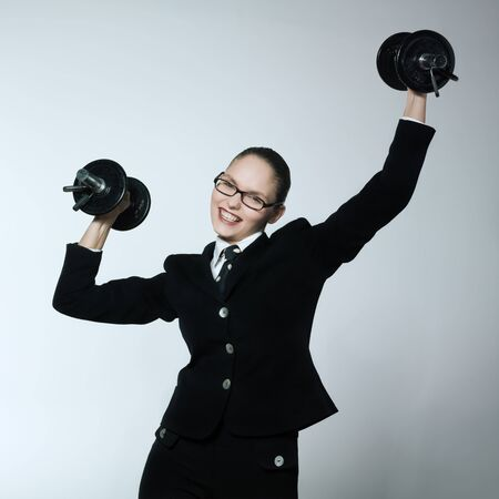 strong toughness: studio shot portrait of one caucasian young bsuiness woman holding weights Stock Photo