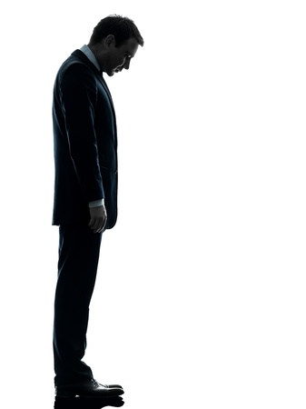 one caucasian sad business man  looking down  in silhouette studio isolated on white background photo