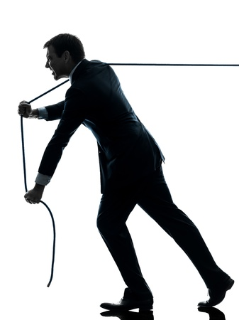 one caucasian business man pulling a rope in silhouette studio isolated on white background photo