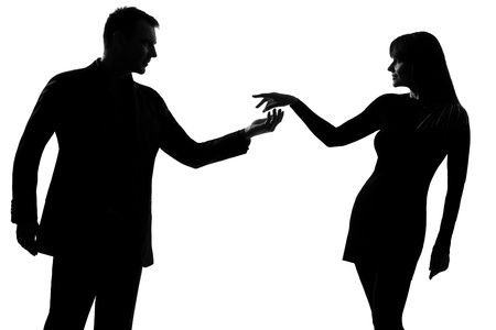 flirting: one caucasian couple man holding out inviting hand in hand  woman in studio silhouette isolated on white background