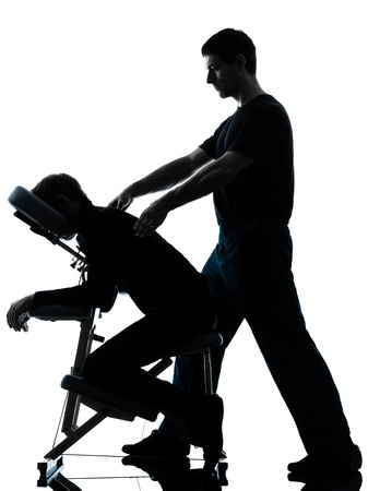massage chair: two men performing chair back massage in silhouette studio on white background