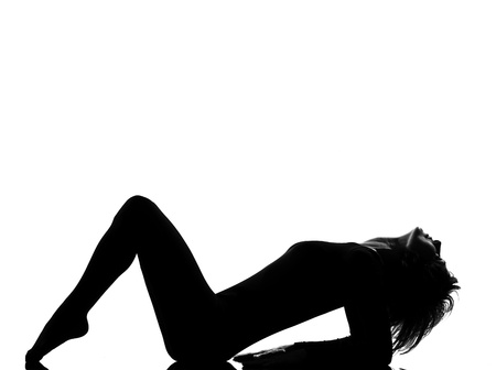 lying on side: woman exercising lying on back fitness yoga stretching in shadow grayscale silhouette full length in studio isolated white background
