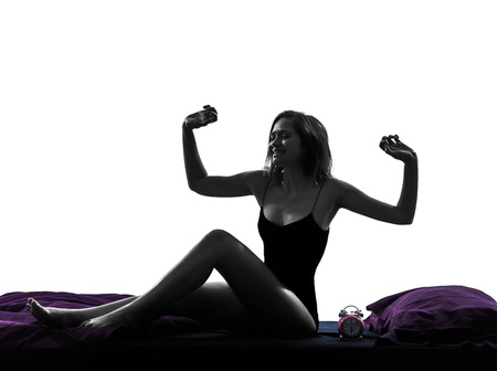 one woman waking up happy stretching in bed silhouette studio on white background photo