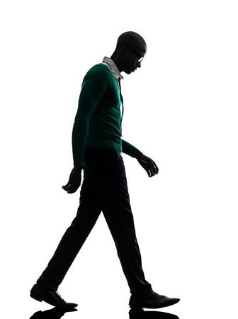one african  black man walking looking down sad  in silhouette studio on white background photo