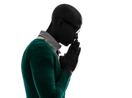 hombre orando: un hombre negro africano pensando silueta orando pensativa en el estudio de la silueta sobre fondo blanco Foto de archivo
