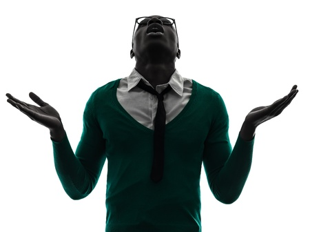 man praying: one african  black man looking up complaigning  in silhouette studio on white background Stock Photo