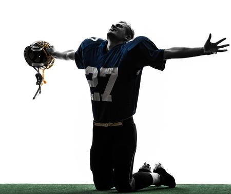 fuball spieler: ein kaukasisch american football player Mann triumphierend in Silhouette Studio isoliert auf wei�em Hintergrund