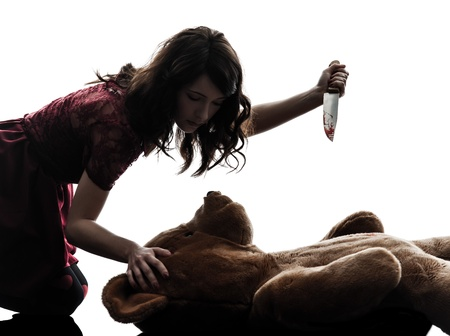 slasher: one caucasian strange young woman killing her teddy bear  in silhouette white background Stock Photo